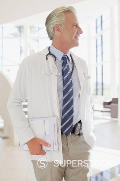 Doctor holding clipboard in hospital : Stock Photo
