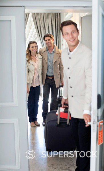 Stock Photo: 1775R-30684 Portrait of bellman opening hotel room door with couple in background