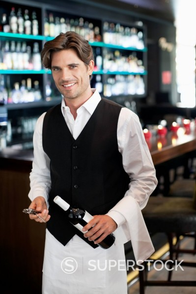 Portrait of smiling sommelier holding bottle of wine in bar : Stock Photo