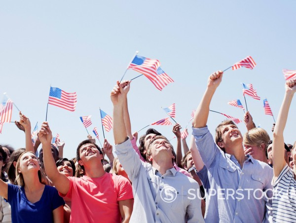 Stock Photo: 1775R-30721 Smiling people waving American flags and looking up in crowd