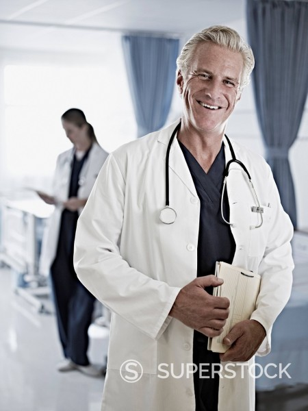 Stock Photo: 1775R-30725 Portrait of confident doctor holding medical record in hospital