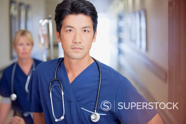 Portrait of serious nurse in hospital corridor : Stock Photo