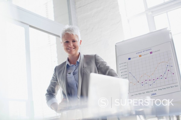 Portrait of smiling businesswoman next to graph in conference room : Stock Photo