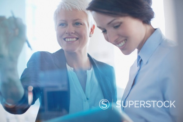 Smiling businesswomen working together in office : Stock Photo