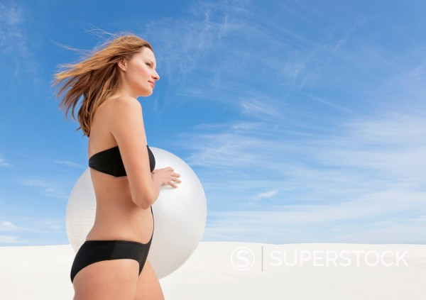 Stock Photo: 1775R-30776 Woman in bathing suit holding fitness ball on beach