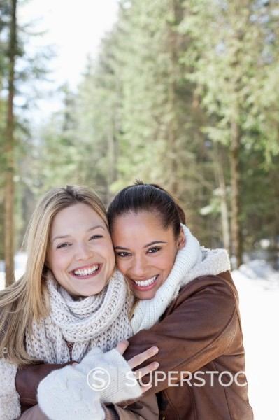 Stock Photo: 1775R-30810 Portrait of smiling friends hugging in snowy woods