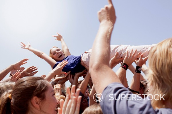 Enthusiastic woman crowd surfing : Stock Photo