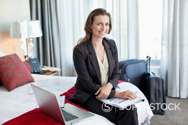 Stock Photo: 1775R-30843 Portrait of smiling businesswoman with paperwork and laptop in hotel room