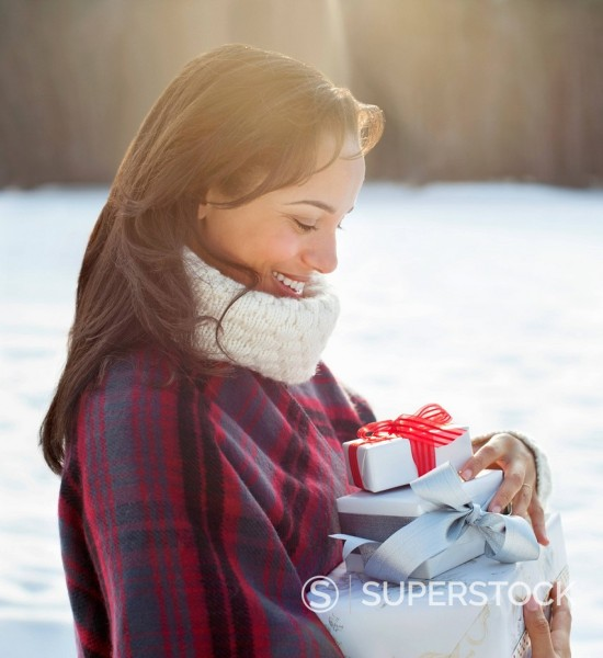 Stock Photo: 1775R-30844 Smiling woman carrying Christmas gifts