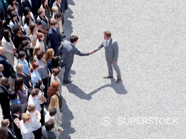 Businessman shaking man's hand in crowd : Stock Photo