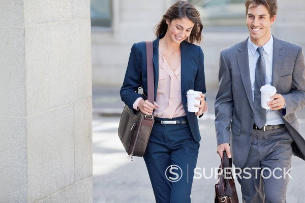 Stock Photo: 1775R-30879 Smiling businessman and businesswoman walking with coffee cups