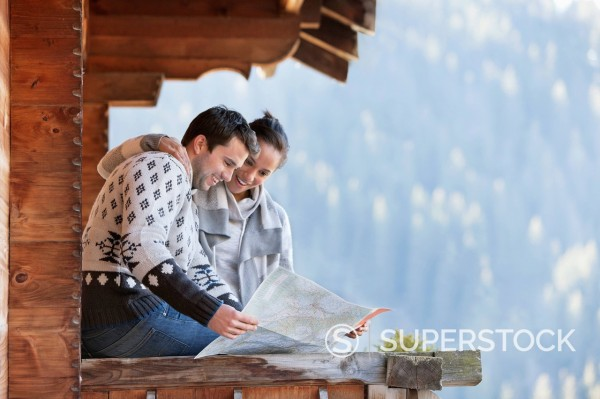 Smiling couple looking at map on cabin porch : Stock Photo