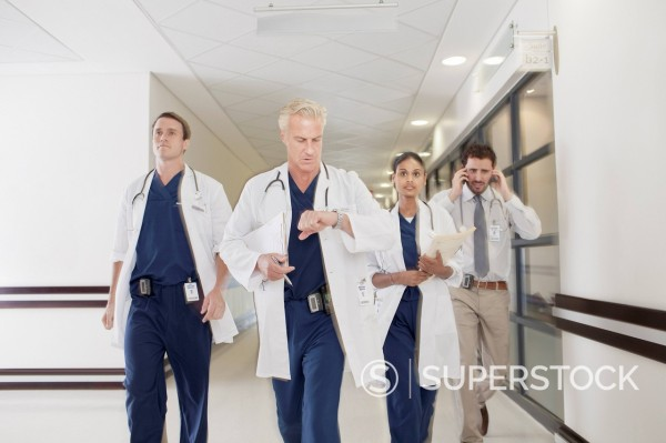 Doctors rushing down hospital corridor : Stock Photo