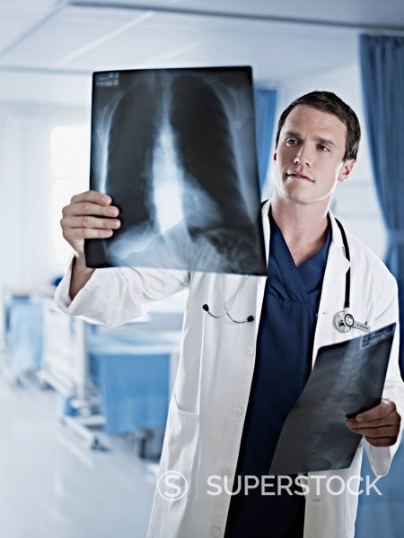 Doctor examining x_rays in hospital room : Stock Photo