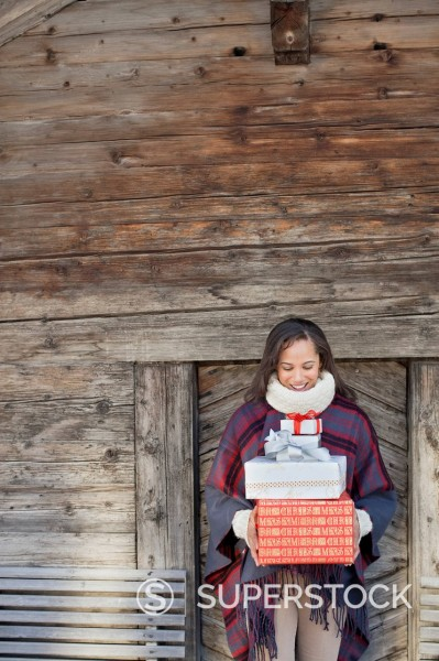 Stock Photo: 1775R-30920 Portrait of smiling woman holding Christmas gifts in front of cabin