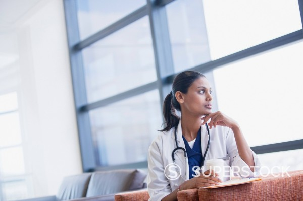 Pensive doctor drinking coffee and looking out window : Stock Photo
