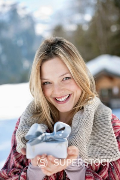 Portrait of smiling woman holding Christmas gift in snow : Stock Photo