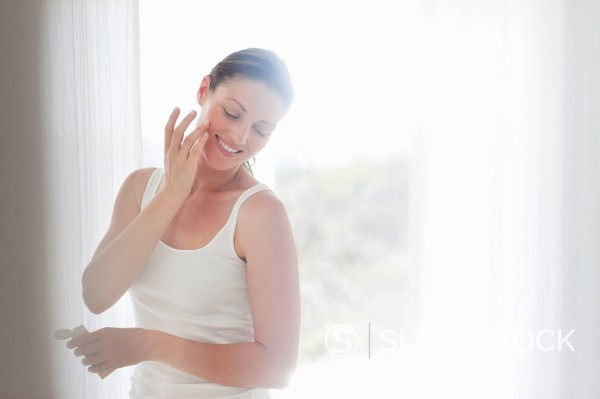 Stock Photo: 1775R-30933 Smiling woman applying moisturizer to face