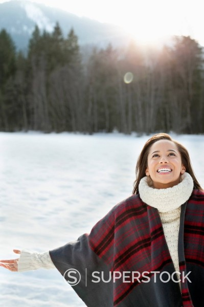 Smiling woman with head back and arms outstretched in snow : Stock Photo