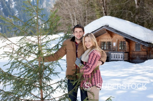 Stock Photo: 1775R-30978 Portrait of smiling couple with fresh cut Christmas tree in front of cabin