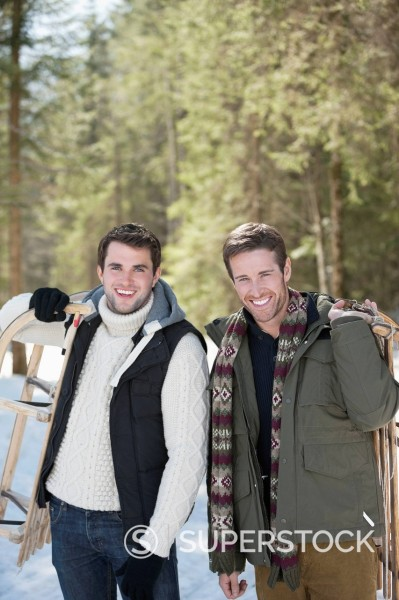 Stock Photo: 1775R-30981 Portrait of friends holding sleds in snowy woods