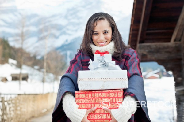 Stock Photo: 1775R-30995 Portrait of smiling woman holding Christmas gifts