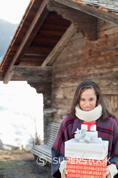Stock Photo: 1775R-30997 Portrait of smiling woman holding Christmas gifts in front of cabin