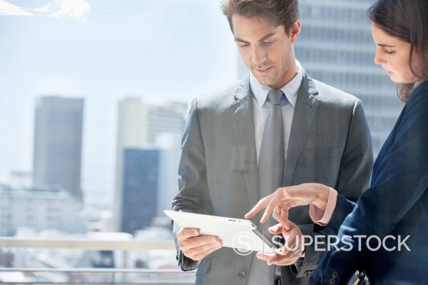 Stock Photo: 1775R-31017 Businessman and businesswoman with digital tablet on urban balcony