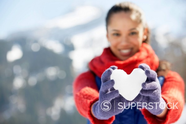 Portrait of smiling woman holding heart_shape snowball : Stock Photo