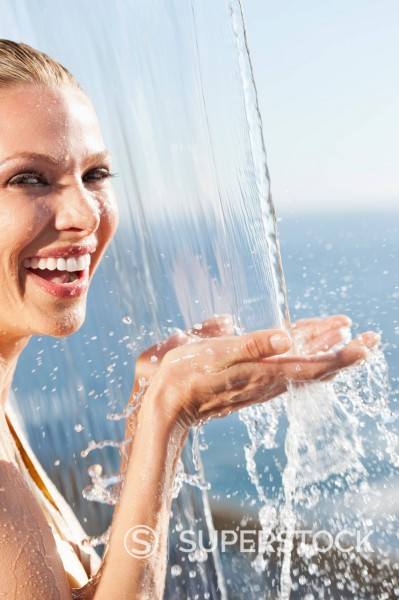 Stock Photo: 1775R-31033 Close up portrait of smiling woman standing under outdoor shower