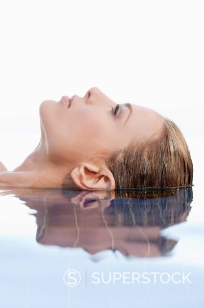 Close up of calm woman laying in infinity pool : Stock Photo