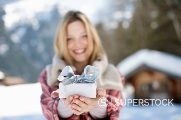 Stock Photo: 1775R-31043 Portrait of smiling woman holding Christmas gift in front of cabin