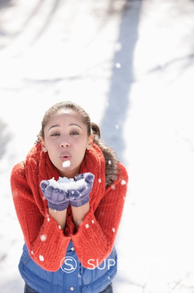 Stock Photo: 1775R-31045 Portrait of woman blowing snow in hands
