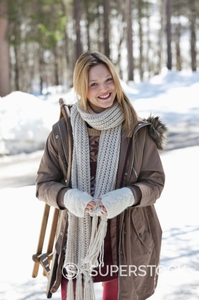 Portrait of smiling woman with sled in snowy woods : Stock Photo
