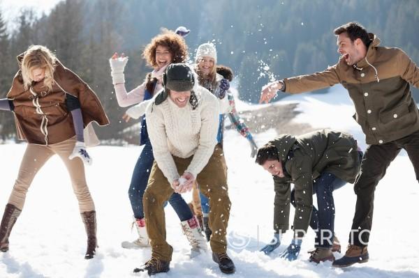 Stock Photo: 1775R-31047 Friends enjoying snowball fight in field