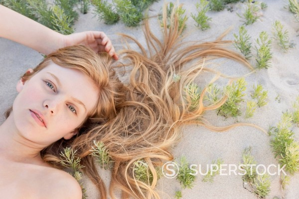 Stock Photo: 1775R-31057 Portrait of woman laying on beach