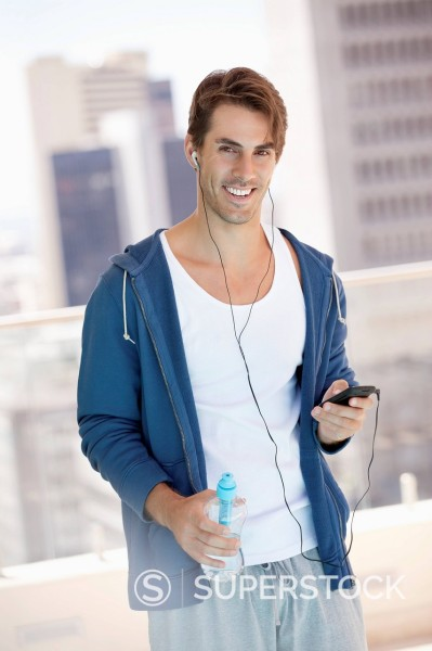 Stock Photo: 1775R-31076 Portrait of smiling man holding water bottle and listening to mp3 player on urban balcony
