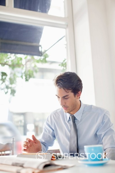 Stock Photo: 1775R-31077 Businessman looking down at digital tablet in café