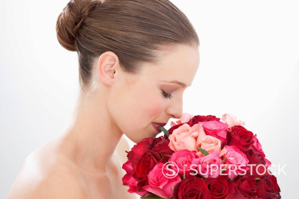 Close up of woman with eyes closed smelling bouquet of roses : Stock Photo
