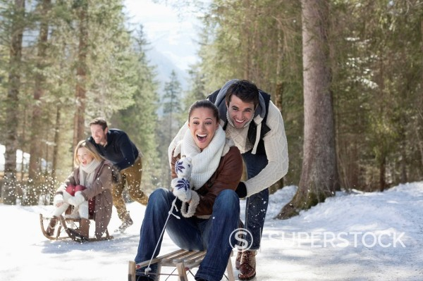 Stock Photo: 1775R-31110 Smiling couples sledding in snowy woods