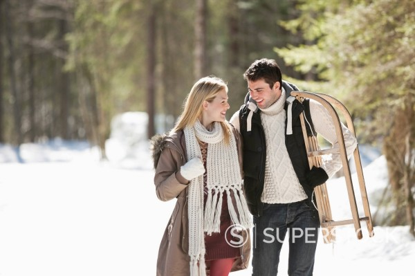 Smiling couple with sled walking in snowy woods : Stock Photo