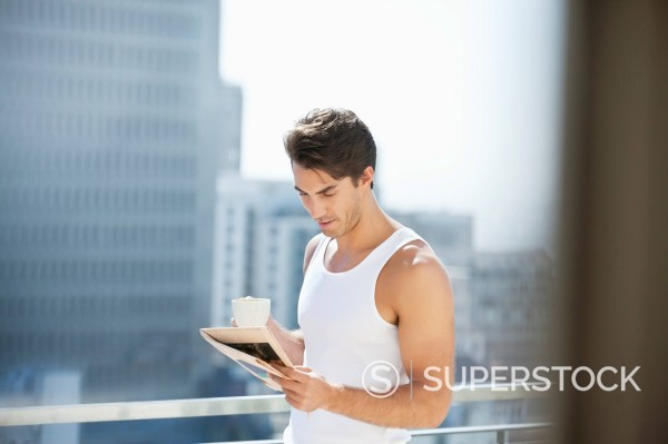 Stock Photo: 1775R-31118 Man drinking coffee and reading newspaper on urban balcony