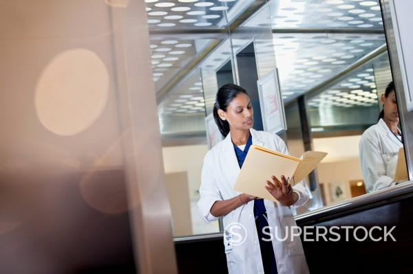 Stock Photo: 1775R-31121 Doctor reviewing medical record in hospital elevator