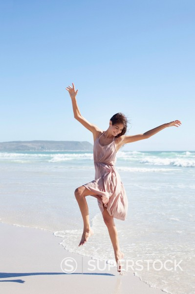 Carefree woman dancing on sunny beach : Stock Photo