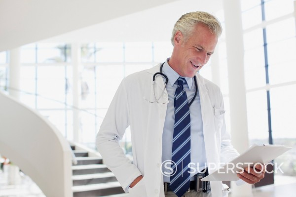 Stock Photo: 1775R-31135 Smiling doctor reviewing medical record in hospital