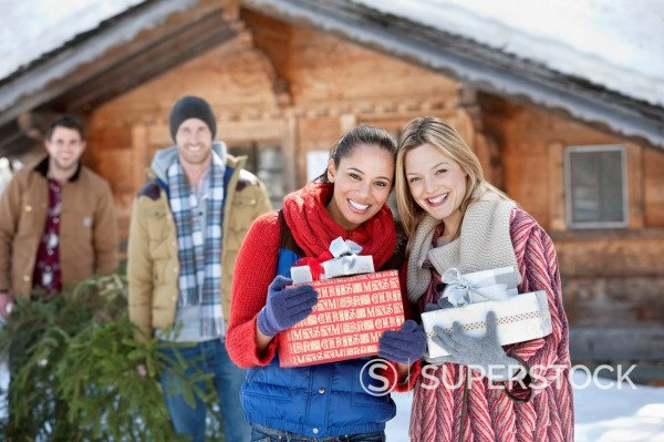 Portrait of smiling friends holding Christmas gifts in front of cabin : Stock Photo