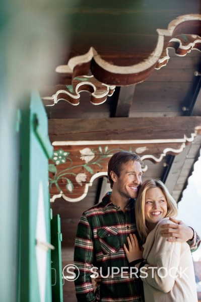 Stock Photo: 1775R-31139 Smiling couple hugging on cabin porch