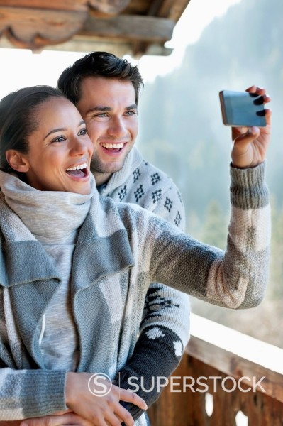 Stock Photo: 1775R-31141 Smiling couple taking self_portrait with camera phone on cabin porch