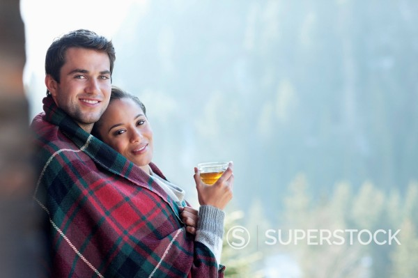 Portrait of smiling couple wrapped in a blanket and drinking hot cider on porch : Stock Photo