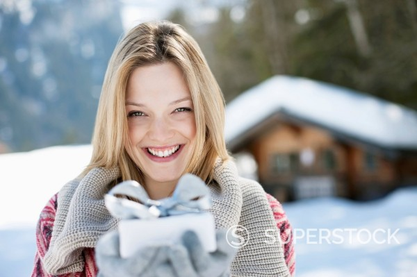 Portrait of smiling woman holding Christmas gift in front of cabin : Stock Photo